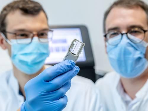 Zwei Männer mit Nasen-Mundschutzmasken, einer hält eine kleine Apparatur in der Hand.