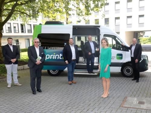 Fünf Männer und eine Frau stehen vor einem Kleinbus