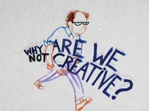 Das Foto zeigt einen Mann der die Aufschrift Why are we not creative im arm trägt.