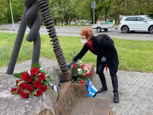 Eine Frau legt Blumen am Mahnmal KZ Stöcken nieder