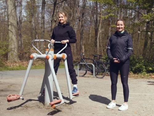Zwei Frauen an einem Fitnessgerät unter freiem Himmel.