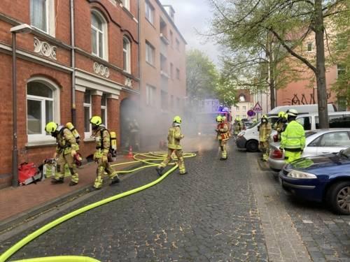 Brandrauch strömt aus einem Hauseingang.