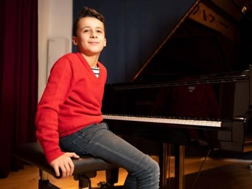 Ein Junge am Klavier.