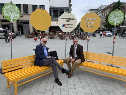 Zwei Personen lächelnde Personen auf einer Bank mitten in der Innenstadt.
