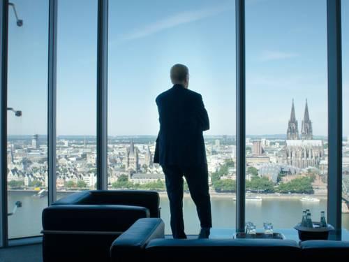 Auf dem Foto zu sehen ist ein Mann der in seinem Büro mit verschränkten armen nach draußen schaut.