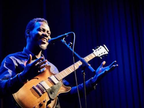 Ein Mann steht auf einer Bühne und singt in ein Mikrofon, um ihn herum strahlt blaues Licht. Eine Gitarre hängt vor seiner Brust, mit beiden Armen macht er eine einladende Geste.