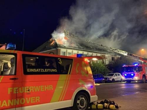 Rote Flammen schlagen aus einem Hausdach.