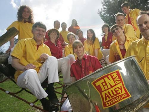 15 Musikerinnen und Musiker tragen gelbe, rote und weiße Kleidung und haben sich auf dem Kletternetz eines Spielplatzes positioniert.