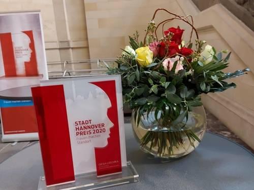 Der STADT-HANNOVER-PREIS neben einer Vase mit Blumen.