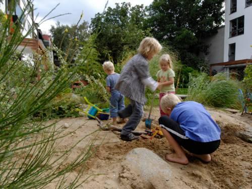 Kinder spielen mit Schaufeln, Baggern und anderen Spielzeugen auf einem Sandhaufen.