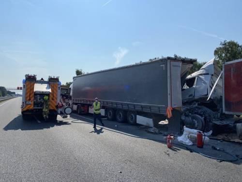 Zwei Lastwagen, die ineinander gefahren sind, stehen neben einem Rettungswagen.