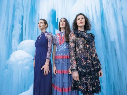 Drei Frauen tragen Kleider, schauen in eine ähnliche Richtung. Hinter den drei Frauen und um sie herum ist eine gefrorene Eislandschaft mit Eiszapfen.