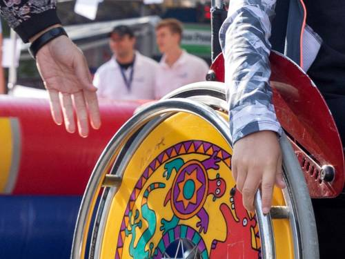 Eine jüngere Person fährt mit einem Rollstuhl, die Hand einer weiteren Person ist daneben.