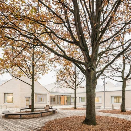 Das Stadtteilzentrum Stöcken mit vier Bäumen im Vordergrund