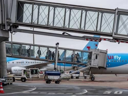 Fluggäste besteigen über einen gläsernen Tunnel ein Flugzeug
