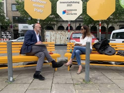 Zwei Personen im Gespräch auf einer Bank in Hannovers Innenstadt.