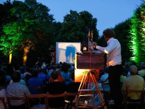 Ein Mann bedient einen Projektor uns wirft die Szene eines Films unter freiem Himmel auf eine Leinwand, Publikum verfolgt den Film.