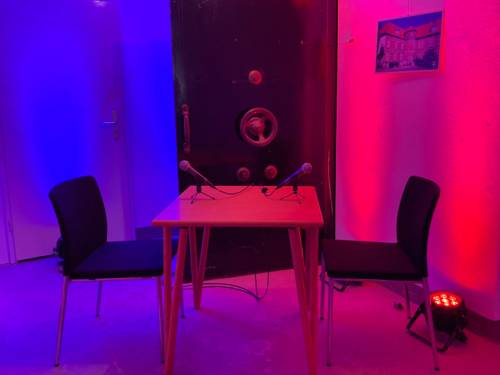 Neben der schweren Panzertür eines Tresors steht ein Tisch, daran zwei Stühle und darauf zwei Mikrofone. Scheinwerfer tauchen die Szene in Rot- und Blautöne.