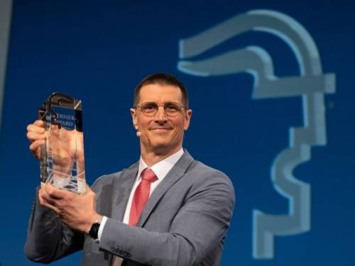 Mann hält gläsernen Pokal in den Händen