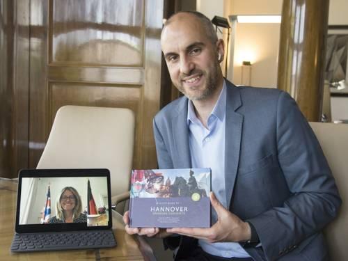 Ein Mann hält einen Reiseführer in den Händen und lächelt in die Kamera, neben ihm steht ein Laptop, auf dem eine Frau in einer Videokonferenz zu sehen ist, auch sie lächelt