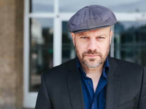 Porträtfoto: Ein Mann trägt Mütze, Bart, Sakko und ein offnenes Hemd und schaut in die Kamera.