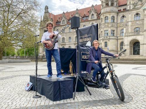 Ein Mann steht auf einer kleinen Bühne, die von einem umgebauten Fahrrad gezogen wird; auf dem Rad sitzt eine Frau. Im Hintergrund das Neue Rathaus in Hannover.