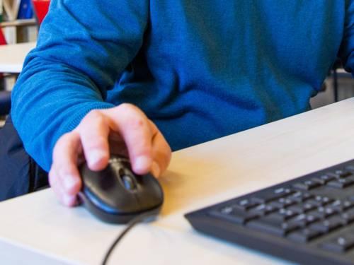 Jemand benutzt einen Computer und bedient eine Maus.