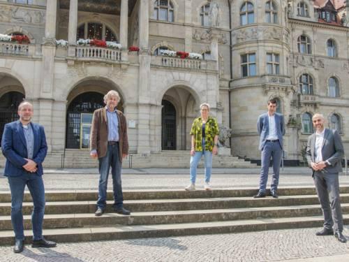 Fünf Personen auf der Treppe vor dem Neuen Rathaus