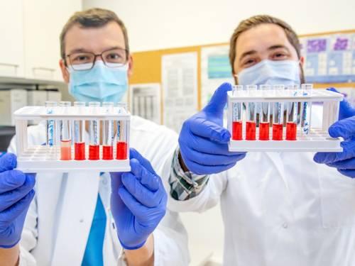 Zwei Männer in weißen Kitteln halten Behälter mit Reagenzgläsern in den Händen.