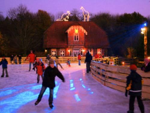 Kinder beim Eislaufen vor einem weihnachtlich geschmückten Fachwerkhaus