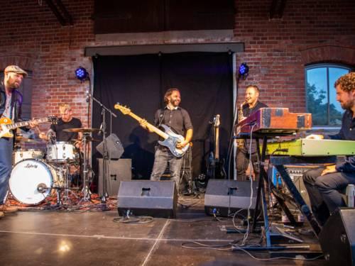 Fünf Musiker spielen auf ihren Instrumenten auf einer Bühne unter einem Scheunenvordach.