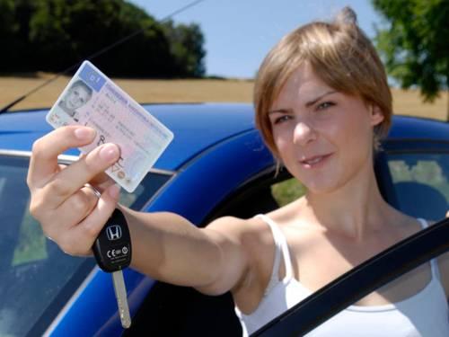Eine Frau zeigt ihren Führerschein und steht hinter einer Autotür. Außerdem hat sie einen Autoschlüssel in ihrer Hand.