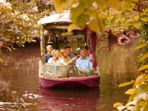 Menschen in einem kleinen Ausflugsboot auf einem kleinen Fluß.