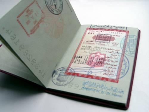 Aufgeschlagene Seite eines Reisepasses mit Ein- und Ausreisestempeln