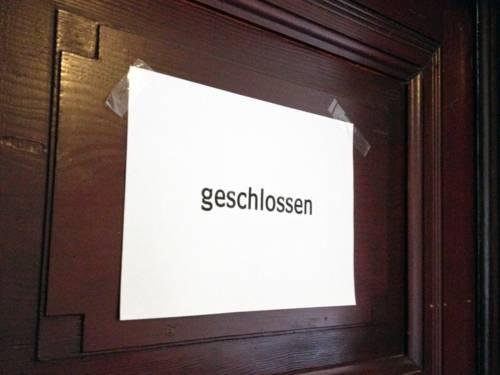 """Eine dunkle Holztür, an der ein weißes Blatt Papier mit der Aufschrift """"geschlossen"""" hängt"""