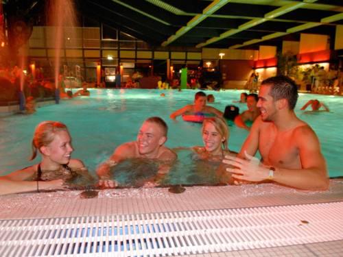 Zwei junge Frauen und zwei junge Männer am Rand eines Schwimmbeckens. Alle vier lächeln und im Wasser sind weitere Badegäste und zwei Wasserfontänen zu sehen.