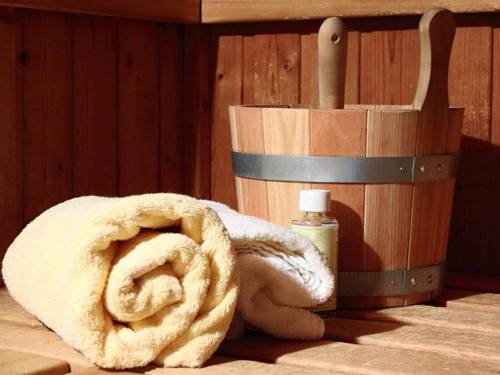Handtuch, Holzgefäß mit Schöpfkelle, Aromaöl auf einer Saunabank