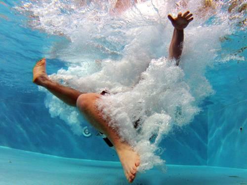 Unterwasserfoto von einer männlichen Person nach einem Sprung ins Wasser, die Person ist nahezu ganz in eine Wolke aus Luftblasen gehüllt