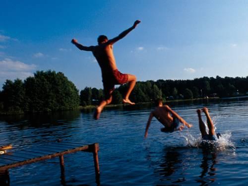 Jungen springen von einem Steg ins Wasser