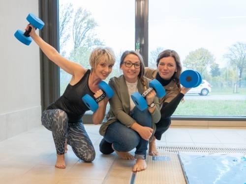 Drei Damen, teils in sportlicher Kleidung, sitzen am Rand eines Schwimmbeckens und halten blaue Hanteln in den Händen.
