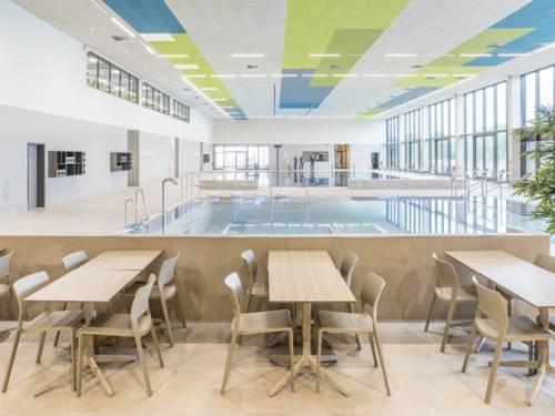 Tische und Stühle, im Hintergrund ein Schwimmbecken