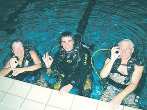 Drei Taucher im Hallenbad, die das OKAY-Zeichen geben