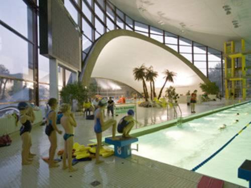 Kinder stehen wartend in einer Reihe, um ins Schwimmerbecken zu springen, im Hintergrund einige Palmen vor einer großen Fensterfront
