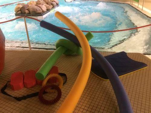 Poolnudeln, Schwimmgürtel, Tauchringe, Schwimmbrett auf gekacheltem Bodem am Rand eines Schwimmbeckens