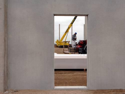 Blick durch einen Durchgang in einer Betonwand.