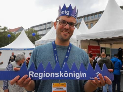 """Junger Mann mit Pappkrone auf dem Kopf auf der """"Regionskönig"""" steht. In der Hand hält er die Krone in aufgeklappter Form mit Aufschrift """"Regionskönigin"""""""