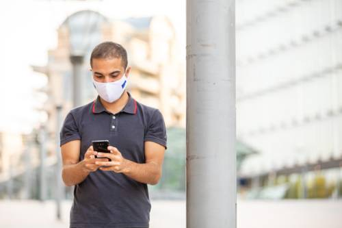 A man with a face mask looking at his smartphone