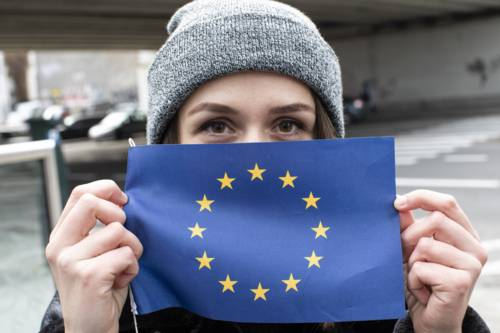 A person holding an EU flag