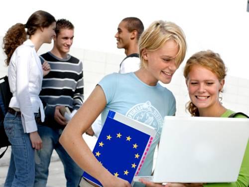 Junge Menschen im Gespräch, eine Person trägt eine Mappe mit EU-Symbol