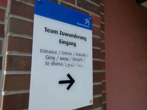 """Schild an einem Eingang auf dem """"Team Zuwanderung Eingang"""" in verschiedenen Sprachen steht"""